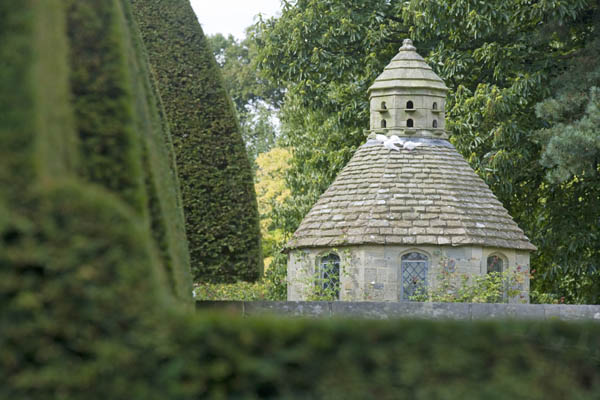 The dovecote seen over the topiary hedges at Nymans Gardens, West Sussex